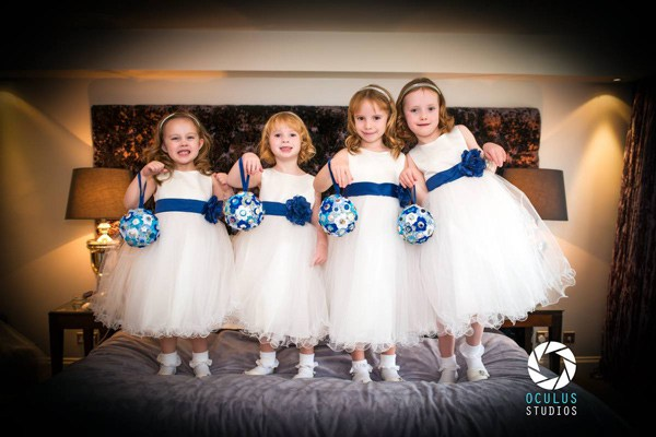 Four young bridesmaids in dresses standing on bed