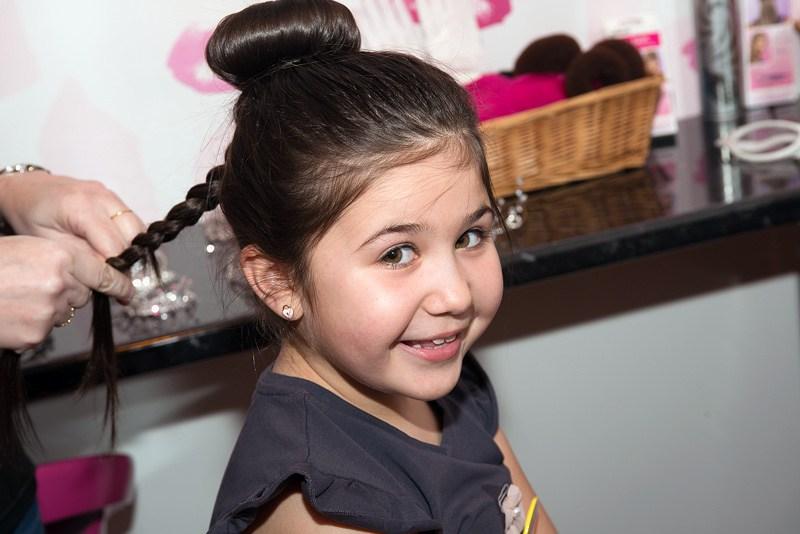 Little girl having her hair platted smiling excitedly