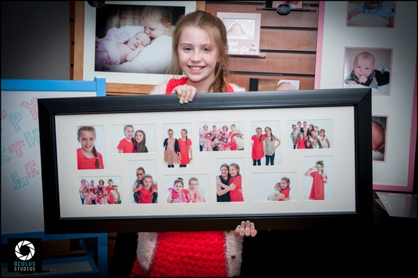 Party princess holding photo frame with party photos mounted